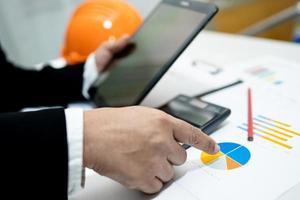 arkitekt eller ingenjör som arbetar med projektredovisning med diagram och bygghjälm i regeringsställning, konstruktionskontokoncept. foto