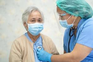 läkare som använder stetoskop för att kontrollera asiatisk senior eller äldre gammal damkvinnapatient som bär en ansiktsmask på sjukhus för att skydda infektion covid-19 coronavirus. foto