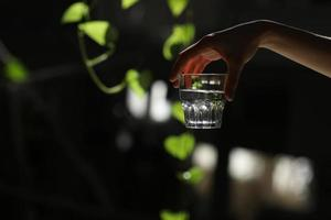 kvinna som rymmer ett glas vatten på en mörk bakgrund. glas rent vatten i handen. hälsosam livsstil. foto