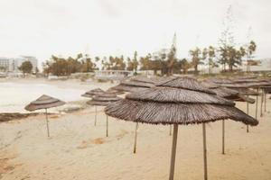 vackra halmparaplyer på stranden på den tomma stranden, ljusblått vatten och himmel, paradis tropisk strand, avkopplande tid ,, fantastisk utsikt, inga människor, solnedgång bakgrund. selektivt fokus foto