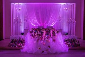 festbord för bruden och brudgummen dekorerat med tyg, ljusstake och blommor. bröllop dekoration med lila ljus foto