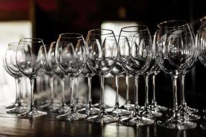 tomma vinglas. vackra nya glas för vin från glasställ i jämna rader på ett träbord i en restaurang. selektivt fokus foto