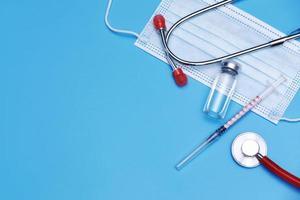 medicinsk flaska, injektionsflaska, spruta, stetoskop och ansiktsmask på blå bakgrund med kopieringsutrymme. vaccinationssession och immunförbättring. foto