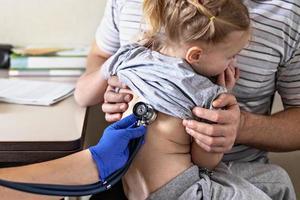 liten flicka i armarna på sin far på läkarmottagningen på kliniken. läkaren undersöker barnet, lyssnar på lungorna med ett fonendoskop. behandling och förebyggande av luftvägsinfektioner. foto