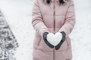 kvinnors händer i varma grå vantar med ett snövitt hjärta. begreppet alla hjärtans dag foto