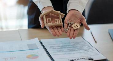 husmodell och nyckel på bordet för finans- och bankkoncept. hemköpslånekoncept. foto