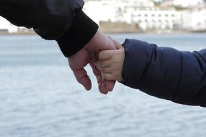far och son som håller hand foto