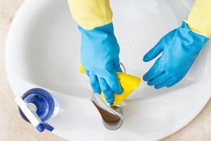 händer med handskar som rengör ett badrum med en gul trasa. desinfektion eller hygienkoncept foto