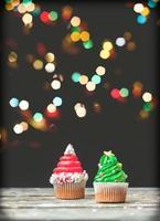 vaniljmuffins med juldekoration, på mörk bakgrund med färgglada julbelysning foto