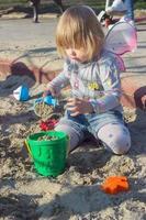 vacker liten flicka med älvvingar som spelar sanden foto