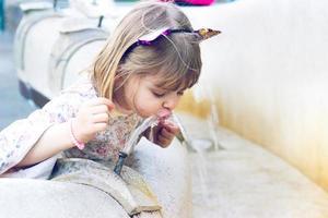liten flicka dricksvatten på offentliga fontän foto