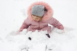 liten flicka sitter i snön och leker med nysnö som föll över natten foto