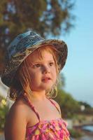 porträtt av en vacker liten flicka med en stråhatt på stranden, med kopia utrymme foto