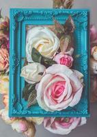 komposition gjord av fotoram och konstgjorda blommor i pastellfärger foto