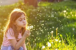liten flicka i parken på den soliga sprind dagen blåser maskros foto