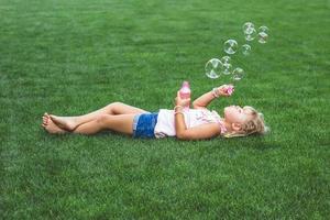 liten flicka som lägger på gräset och blåser såpbubblor foto