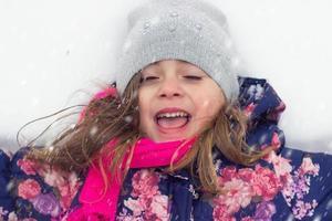 liten flicka njuter av snön foto