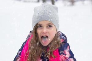 liten flicka som äter snö foto