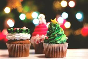 muffins dekorerade till jul, mot färgglada bokeh bakgrund semester bakgrund foto