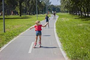 liten flicka njuter av rullskridskoåkning utomhus, på en varm solig dag foto