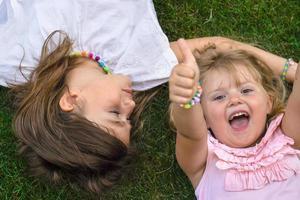 två små flickor lägger på gräset, skrattar och visar tummen foto