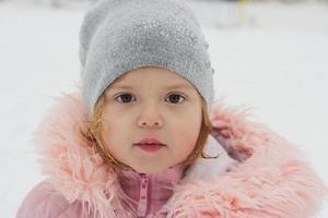 vacker liten flicka, tittar på kameran, vinter porträtt foto