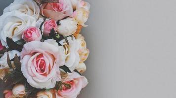 bukett av konstgjorda pastellfärgblommor på grå bakgrund, ovanifrån med kopieringsutrymme foto
