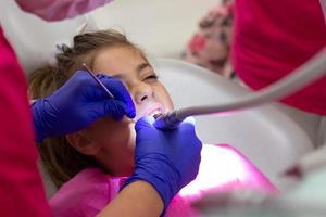 liten flicka vid tandläkarens tid. uppriktig bild av inspektion och tand som behandlas foto