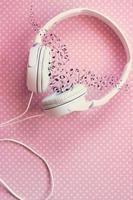 vita hörlurar på rosa bakgrund, med musiknoter foto