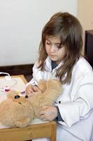liten flicka låtsas vara läkare och leker med sin nallebjörn foto
