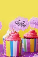 """välsmakande jordgubbsmuffin i färgglad pappersbägarkopp, med """"Grattis på födelsedagen"""", på gul bakgrund. födelsedag bakgrund foto"""