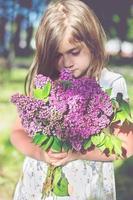 liten flicka som håller lila blommor foto