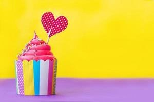 välsmakande jordgubbsmuffin i färgglad pappersbakakopp, med röd hjärttoppare, på gul bakgrund. fest eller alla hjärtans bakgrund foto