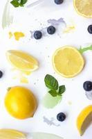 citron, blåbär och mynta lämnar på vit bakgrund med akvarellstreck kreativ sommarbakgrund foto