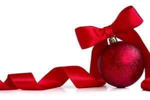 röd julboll, med rött band och rosett, på vit bakgrund med kopieringsutrymme foto