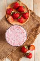 färsk milkshake med jordgubbar. sommardryck med bär i ett glas på träbakgrund. foto