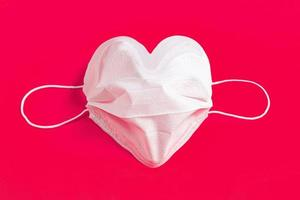 kirurgisk mask i form av hjärta över färgstark bakgrund foto