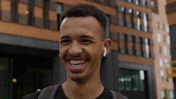 porträtt av ung man som bär trådlösa örsbitar skrattar foto
