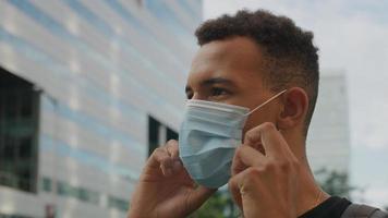 porträtt av ung man justera skyddande ansiktsmask foto