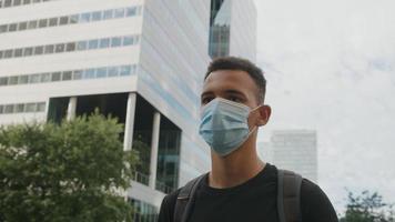 porträtt av ung man som bär skyddande ansiktsmask i staden foto
