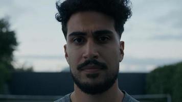 ung man med mustasch och skägg som tittar på kameran foto