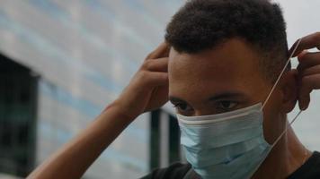 porträtt av ung man sätta på skyddande ansiktsmask foto