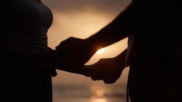 porträtt av unga par som håller händerna på stranden foto