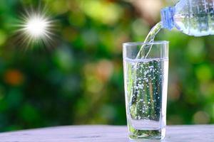 vatten rinner in i ett glas på bord och mineralvatten hälsovård koncept foto