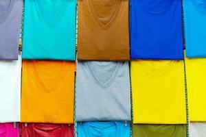 närbild av färgglada t-shirts på galgar foto