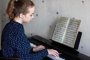ung flicka pianist i processen att spela piano. spelar klassisk musik. livsstil. foto