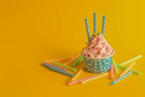 god födelsedagmuffin med ljus på gul färgbakgrund foto