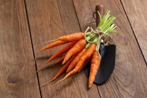 färska baby morötter på trä skärbräda och trä bakgrund foto