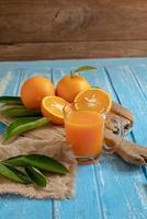 färsk apelsin och ett glas apelsinjuice på en träbordbakgrund foto