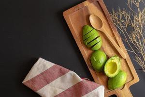 färsk ekologisk avokado skivad i hälften på svart träbord foto